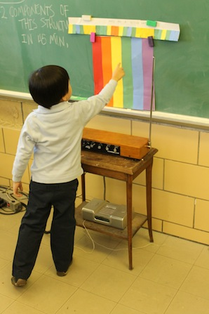 child pointing to color and playing theremin